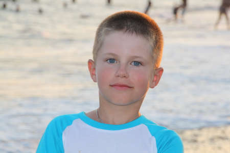 squint: Portrait of a smiling boy with a background of the blue sea