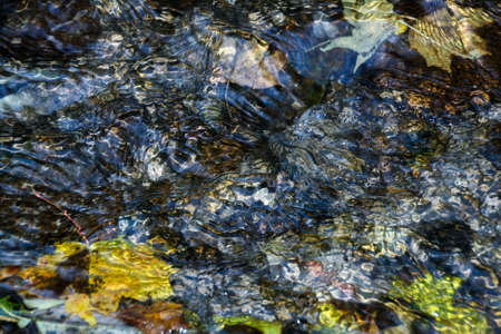rippling: background of pebbles seen through rippling water in the sun