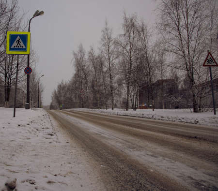snowcovered: Empty snow-covered town road on the background of trees