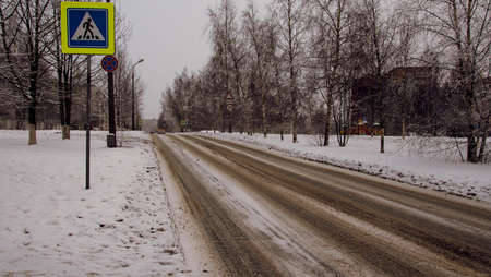 mud snow: Empty snow-covered town road on the background of trees