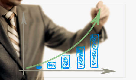 Businessman drawing rising graph, development and growth concept, increase of positive indicators in entrepreneurship.