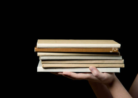 hidef: stack of books in a childs hand on a dark background