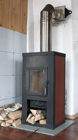 tradional: Tradional rustic metal stove and stacked firewood