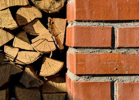 woodshed: red brick woodshed on a background of stacked wood Stock Photo