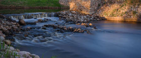 threshold: the threshold of stones on the river on the background of green grass Stock Photo