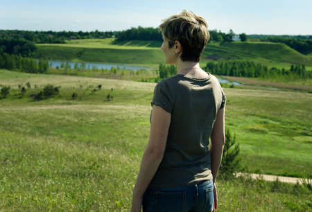 forlorn: lonely woman standing with her back on the green field