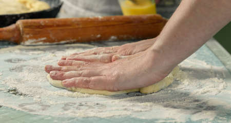 kneading: female hands in flour kneading dough on the table Stock Photo