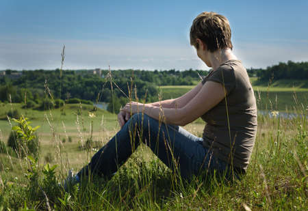introspective: lonely woman sitting with her back on the green field