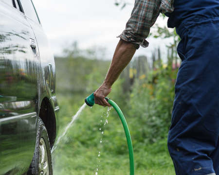 sudsy: man washes his car on a background of green garden Stock Photo