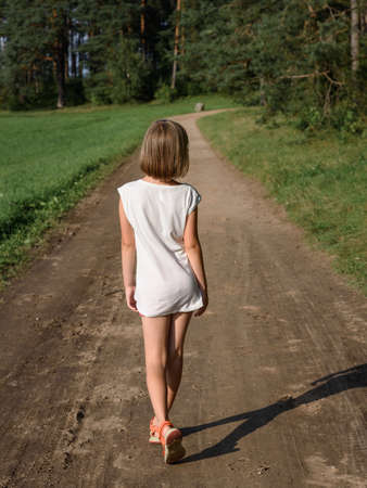 discoverer: little girl walking along summer road into the woods