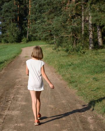 descubridor: little girl walking along summer road into the woods