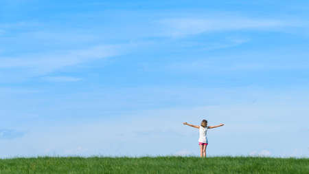 happy little girl standing on a mountain with blue sky background Stock Photo