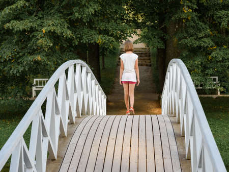 discoverer: little girl walking on the bridge in the summer into the woods