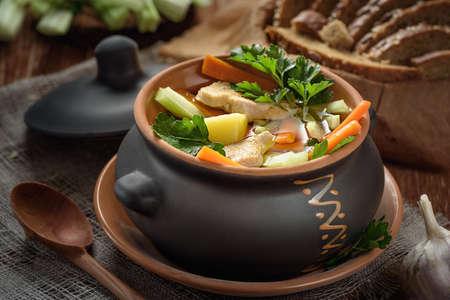 plato del buen comer: soup in the pot, bread, wooden spoon on the table closeup