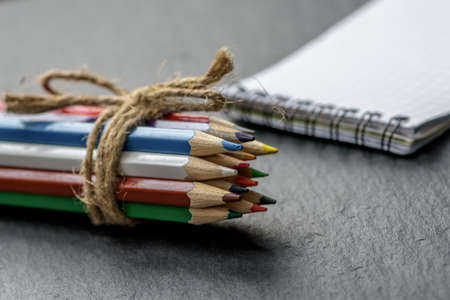 Colored pencils tied with twine on background of notebookon a wooden table