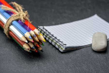 Colored pencils tied with twine on background of notebook and eraser on a wooden table