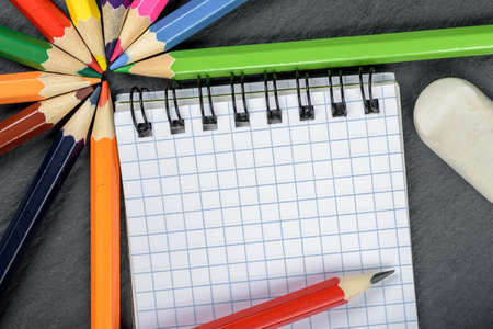 colored pencils, eraser, notebook closeup on wooden table