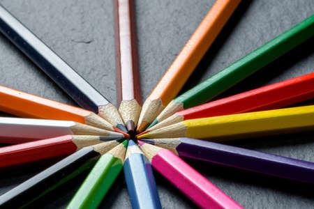Many different colored pencils neatly folded on wooden table background