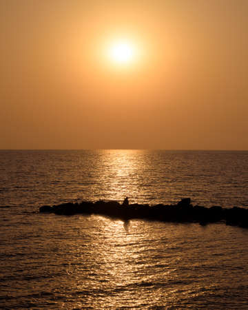 Vertical shot of the quiet summer sunset on the sea, the sun is reflecting in the water and illuminating the silhouette of a man sitting on the breakwater Stock Photo