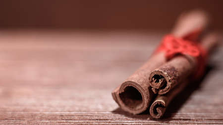 Horizontal shot of cinnamon sticks tied with red ribbon closeup on wooden background blur. Copy space. Stock Photo