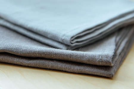 Manufactures industrial textile - grey towels pile isolated on wooden background. Banco de Imagens