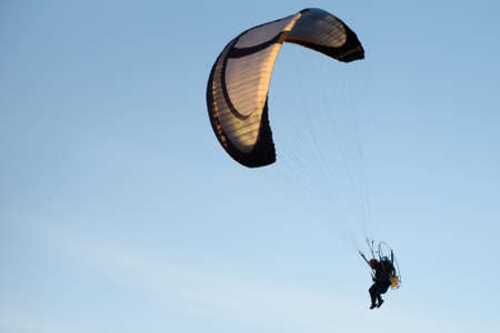 Paraglider fly with paramotor flying in the air on blue sky background.