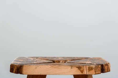 Empty rough wooden table top of old stool in blur on a gray background. Side cut close-up. Photo with for copy space.