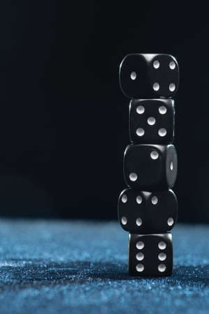 Vertical shot of five black dice on each other of different denominations on a blue background.