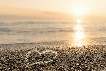 Heart drawn on pebbles of a beach at sunset. The concept of romance and love. 免版税图像