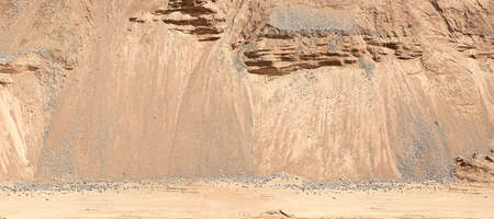The road at a sand quarry on the background of sandy mounds. Industrial sand quarry. Stock Photo