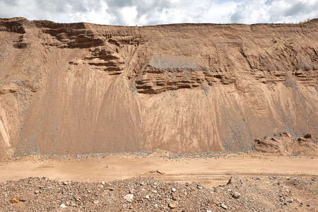The road at a sand quarry on the background of sandy mounds and sky.