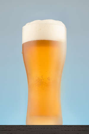 Vertical shot of beer glass close-up on a blue background. Misted glass of beer with foam.