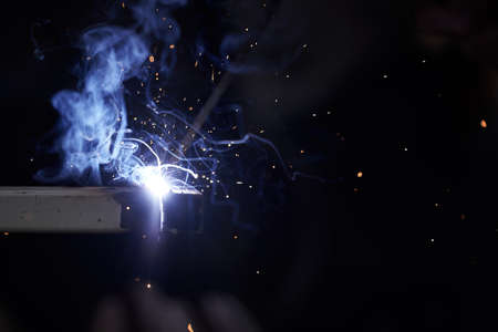 Welding works in the dark. Sparks and blue light when welding.