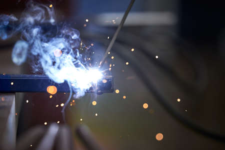 The connection of two parts by welding close-up. Welding work. Sparks fly in different directions.