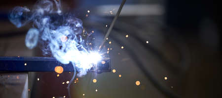 The connection of two parts by welding close-up. Sparks and blue light when welding.