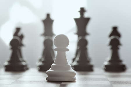 Alone against everyone, chess white pawl against opposite army on gray background.