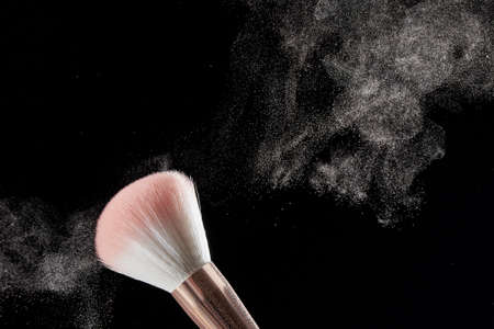 Make-up brush with powder on it and heap of powder on black background. Photo with copy space.