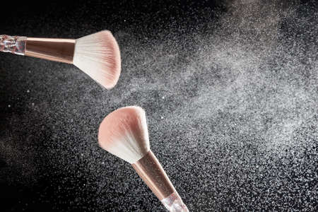 Make-up brushes with powder on it and heap of powder on black background. Photo with copy space.