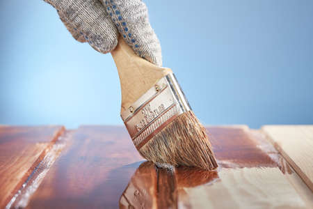 Horizontal shot of man's hand with a paint brush painting wooden surface on a blue background. Imagens