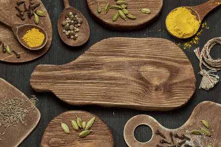 Horizontal shot of spices on wooden cutting boards of different shapes on a dark background.
