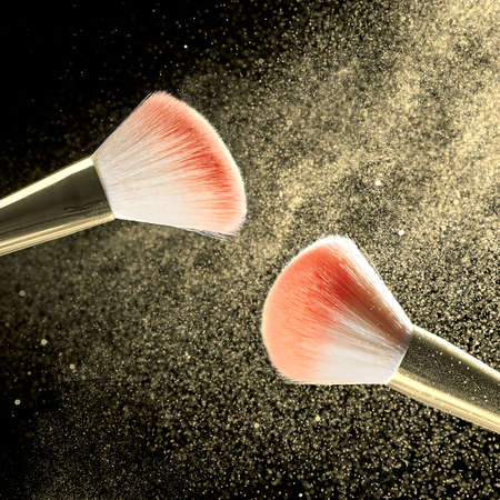 Square shot of two make-up brushes with powder on it and heap of golden powder on black background.