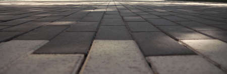 Horizontal shot of endless stone road. The Park path is covered with tiles.