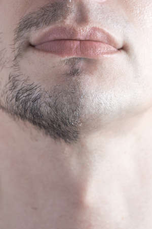 Vertical shot of man shaving concept. A close-up of a man's half-shaven chin. Stok Fotoğraf