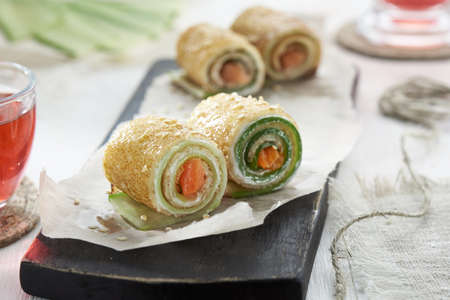 Homemade pancakes rolls with red fish, soft cheese and cucumber. Фото со стока