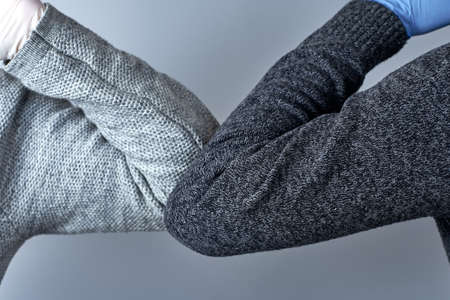 Horizontal shot of two people bump elbows to avoid coronavirus on a gray background. 스톡 콘텐츠