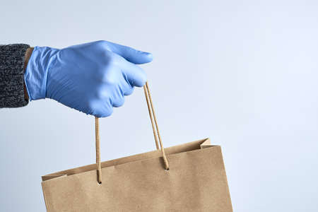Hand in blue rubber gloves holds a paper bag. Safe shopping concept. Food delivery during the quarantine of the coronavirus pandemic.
