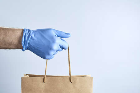 Horizontal shot of hand in a blue rubber glove holds out a paper bag on a gray background. Photo with copy space.
