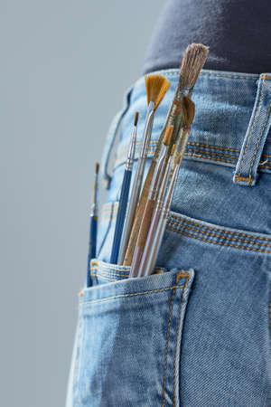 Vertical shot of brushes in pocket of the girl's jeans on a gray background. Artist painting concept. 스톡 콘텐츠
