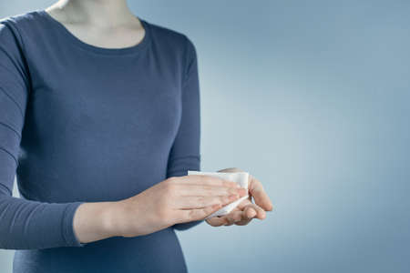 Horizontal shot of woman cleaning her hands by using white antibacterial napkin on gray background.