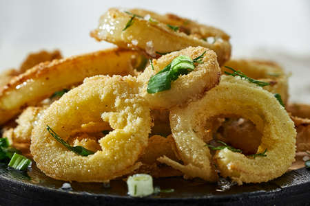 Horizontal shot of Golden Fried Onion Rings sprinkled with greenery close-up. Banque d'images